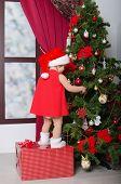 Child Dressed As Santa Decorates Christmas Tree