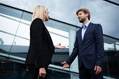 Confident businesswoman discussing with employee outside office
