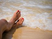 summer, beach, leisure and body part concept - closeup of woman feet on the beach