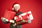 Santa man holding pile of giftboxes