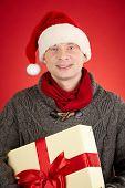 Santa man holding big giftbox tied up by red ribbon