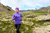 Running woman exercising - trail runner athlete. Fit female sport fitness model training jogging outdoors living healthy lifestyle in beautiful mountain nature, Snaefellsjokull, Snaefellsnes, Iceland.