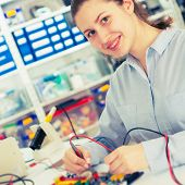 girl with a tester and a printed circuit board