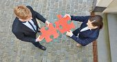 Looking down on two business people solving a big red jigsaw puzzle