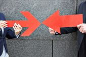 Two business people pointing with two big red arrows to each other