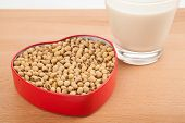 pic of soybean milk  - Soy milk in glass with soybeans in heart shape box on wood table - JPG