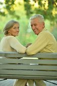 stock photo of copulation  - Amusing senior couple sitting on bench in park - JPG
