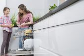 pic of dishwasher  - Happy mother and daughter placing glasses in dishwasher at kitchen - JPG
