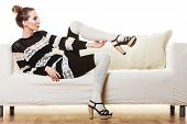 picture of tight dress  - Fashion young woman in full length. Girl in fashionable striped dress high heels posing on white couch. ** Note: Soft Focus at 100%, best at smaller sizes - JPG
