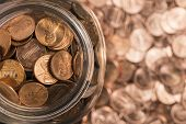picture of abraham  - A jar of pennies surrounded by pennies - JPG