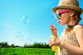 stock photo of country girl  - Pretty little girl blows bubbles on a meadow in summer day - JPG