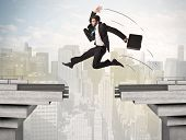 pic of gap  - Energetic business man jumping over a bridge with gap concept - JPG
