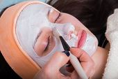 foto of rubber mask  - Spa therapy for young woman receiving facial mask at beauty salon - JPG