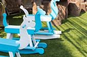picture of paint horse  - blue and white painted rocking horse in the garden - JPG