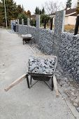 image of wheelbarrow  - wheelbarrows full with gravel at work site - JPG