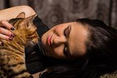 image of bengal cat  - Young beautiful brunette holding a Bengal cat - JPG