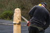 pic of man chainsaw  - The making of an owl sculpture by a chainsaw sculptor here in the midway stage - JPG