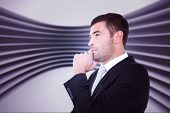 stock photo of frown  - Frowning businessman thinking against abstract room - JPG