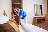 stock photo of maids  - Image of maid making bed in hotel room - JPG