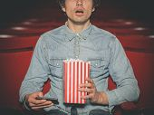 image of popcorn  - A young man is sitting in a cinema and is watching a film while holding his smartphone and a bucket of popcorn - JPG