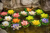 image of cultural artifacts  - Colorful artificial lotus in the in the pond of the wishing well in Thailand - JPG