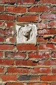 image of gargoyles  - Aged crumbling street wall background with red bricks texture and gargoyle - JPG