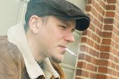 pic of newsboy  - Cool guy in aviator jacket and newsie cap relaxes against a glass wall and enjoys his cigarette - JPG