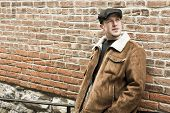 pic of newsboy  - Cool guy rocks an aviator jacket and newsboy cap as he takes a moment to think - JPG