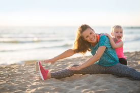stock photo of mother baby nature  - Healthy mother and baby girl stretching on beach in the evening - JPG