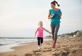 foto of mother baby nature  - Healthy mother and baby girl running on beach