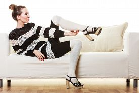image of tight dress  - Fashion young woman in full length. Girl in fashionable striped dress high heels posing on white couch. ** Note: Soft Focus at 100%, best at smaller sizes - JPG