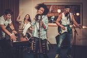 Multiracial music band performing in a recording studio  poster
