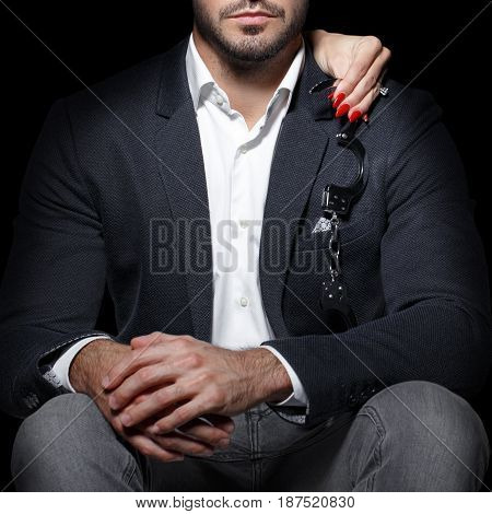 poster of Woman hands holding handcuffs on sexy rich man shoulder bdsm