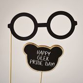 a pair of round-framed eyeglasses attached to a wooden handle and the text happy geek pride written  poster
