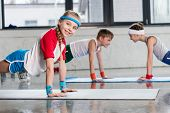 Cute Sporty Kids Exercising On Yoga Mats In Gym And Smiling, Children Sport School Concept poster