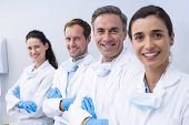 Portrait of smiling dentists standing with arms crossed in dental clinic poster