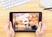 Hand Holding Tablet With Video Sharing On Screen On Wood Table ,internet Marketing Concept. poster