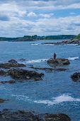 stock photo of striper  - Stiper Fisherman fishing rocky coast Southern Maine - JPG