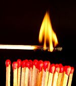 Row of matches with red head and burning match above