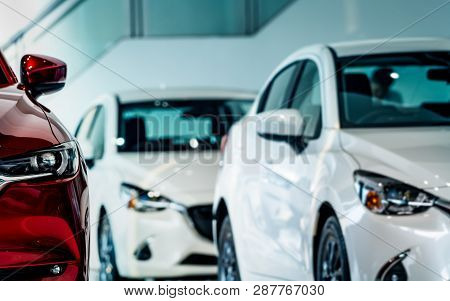 poster of New Luxury Red Shiny Compact Car Parked In Modern Showroom. Car Dealership Office. Car Retail Shop.