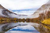 Mountain Lake Among The Snowy Sopki. Taiga On The Mountain Slopes. Mountain Landscape. Tourism. Far  poster