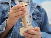 The Boy Holds A Wooden Toy In His Hand. Wooden Key And Keyhole. Puzzle For Children. Key Puzzle. You poster