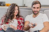 Beautiful Hilarious Young Man Holds A Remote Control, Wifes Cup Of Coffee. During This Man Looks At  poster