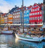 Tourists Walking At Nyhavn Embankment With Moored Tour Boats At Sunset, Copenhagen, Denmark poster