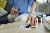 Close Up Of Unrecognizable Senior Woman Taking Pills And Medication Off Table At Home, Copy Space poster