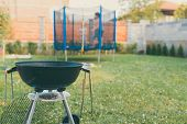 Kettle Charcoal Bbq Barbecue Grill In Garden Or Backyard. Blurred Outdoor Trampoline In The Backgrou poster