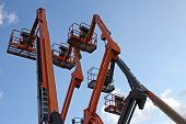 foto of cherry-picker  - A Collection of Orange and Blue Cherry Pickers - JPG