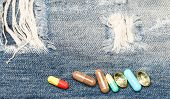 Medicine And Treatment Concept. Drugs On Denim Background. Set Of Colorful Pills. Mixing Medicines.  poster