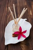 Red Tropical Plumeria Frangipani with Aromatherapy Oil and Cinnamon Stick on wooden table for spa an