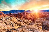 Amazing colors and shape of the sun setting over rocks in Fire Canyon, Valley of Fire State Park, Ne poster